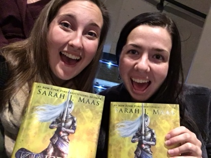 two girls holding copies of kingdom of ash