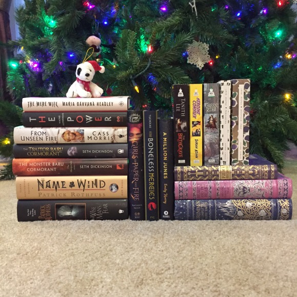eightteen books stacked in front of a glowing christmas tree