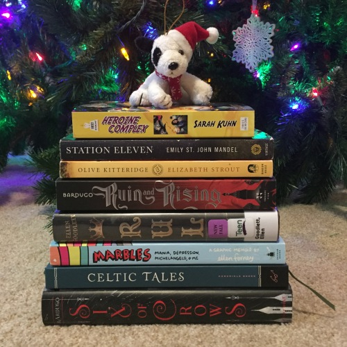 eight books stacked in front of a christmas tree with a mini plush dog on top