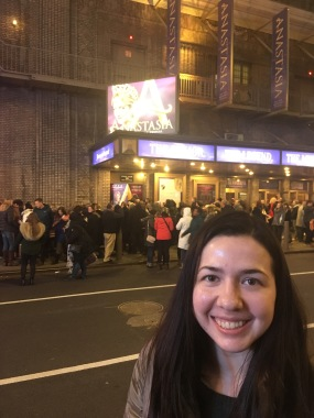 girl standing in street in front of a poster for the Anastasia broadwaymusical
