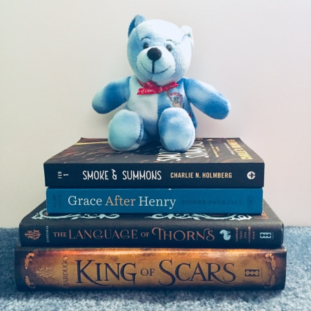 four books in a stack with a toy bear on top