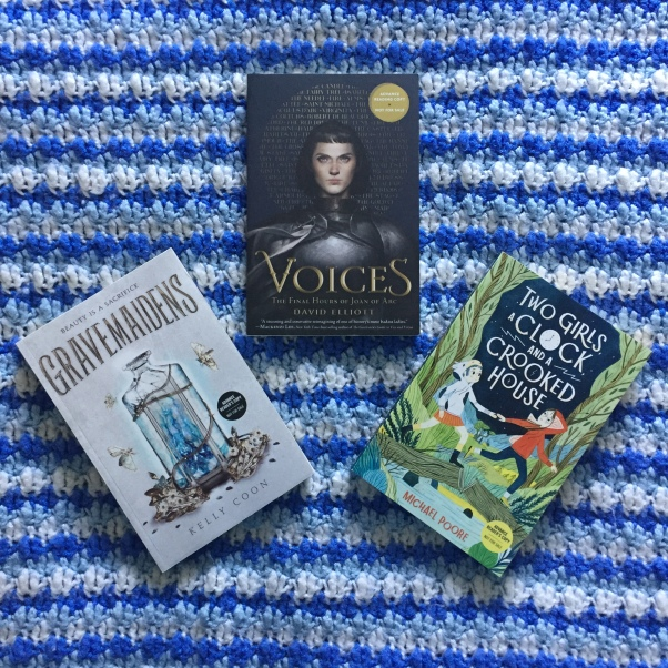 the books 'Gravemaidens,' 'Voices,' and 'Two Girls, a Clock, and a Crooked House' lying against a blue and white blanket