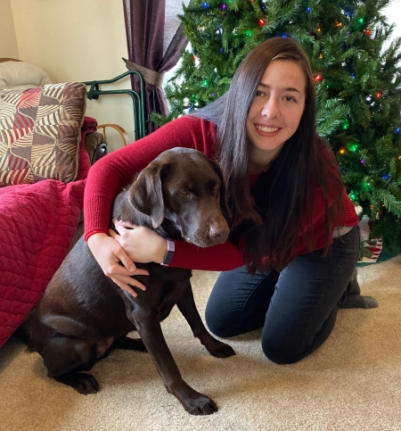 a girl hugging a chocolate labrador in front of a christmas tree