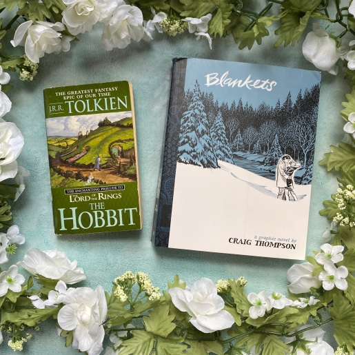 two books on a light blue background surrounded by fake white flowers on a vine