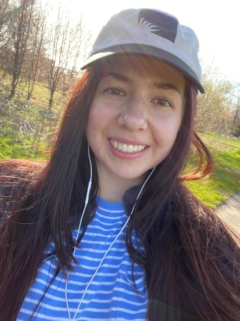 a young woman in a baseball cap and wearing earbuds