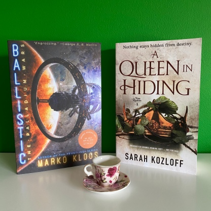 the books 'Ballistic' and 'A Queen in Hiding' standing against a green wall with a tiny pink tea cup in front of them
